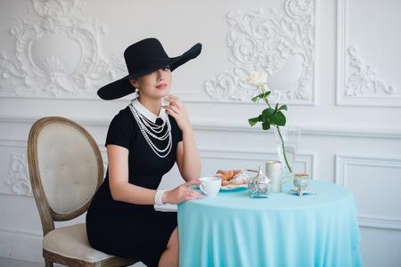 Mujer en el sombrero, al igual que la famosa actriz, croissant de comer y beber té Foto de archivo - 67187186