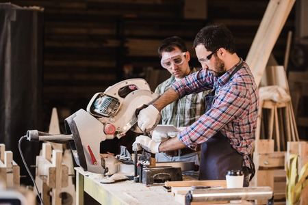 workwoman: Two carpenters cutting a wooden plank with a circular saw.