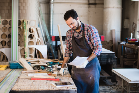 woodwork: Portrait of a carpenter standing in his woodwork studio and holding notebook.