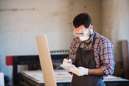 professionally: Horizontal view of professionally dressed carpenter varnishing a board.
