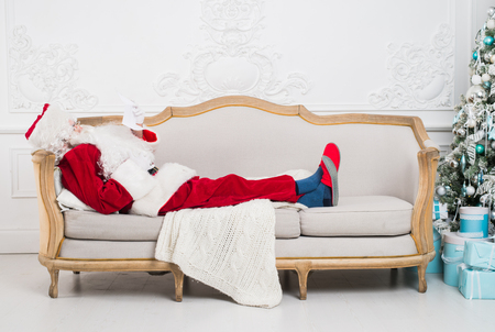 Santa claus using mobile phone at home during christmas time.