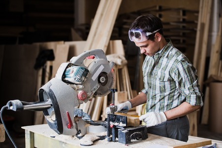 Skilled carpenter cutting a piece of wood in his woodwork workshop, using circular saw with other machinery on the background. Stock Photo