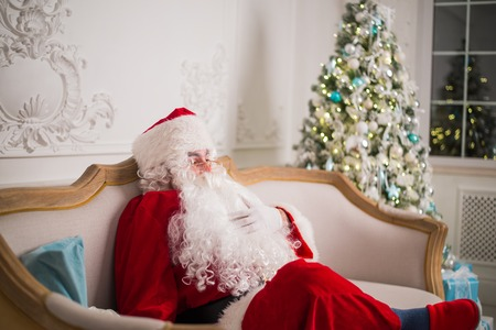 Santa Claus relaxing on sofa against christmas tree at home.