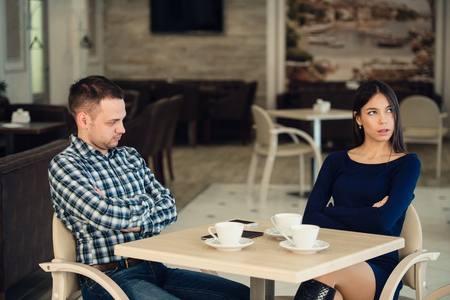 squabble: Young unhappy married couple having serious quarrel at cafe.