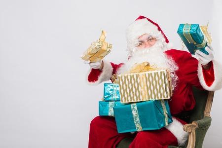 Santa Claus Christmas. Santa holding many Christmas gifts.