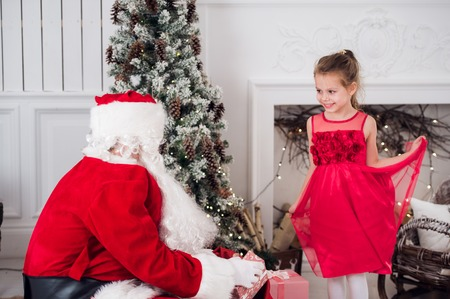 under fire: Santa Claus and children opening presents at fireplace. Kids father in costume wearing beard open Christmas gifts. Little girl helping with present sack. Family under Xmas tree over fire place on background Foto de archivo