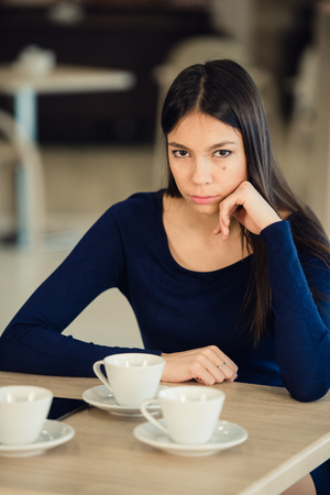 Angry young woman with crossed arms at cafe. Stock Photo