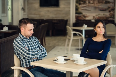 argues: Young unhappy married couple having serious quarrel at cafe.