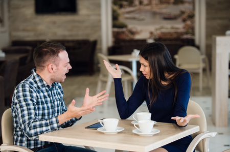 Young couple arguing in a cafe. She's had enough, boyfriend is apologizing. Relationship problems Archivio Fotografico