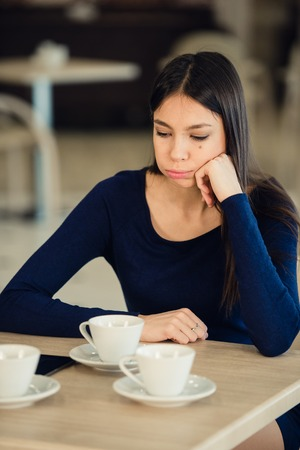 A girl sits in a cafe, props his hand on the cheek. Tired, calm expression