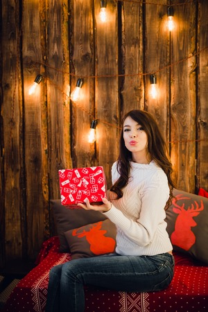 Attractive sensual young female with gift box sending a kiss over glittering background.
