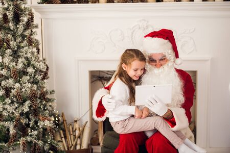 Christmas holiday happy girl santa looking at something on digital touch screen tablet PC, over chimney and tree colorful lights background