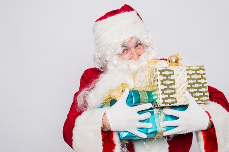 Santa Claus Christmas. Santa holding many Christmas gifts.