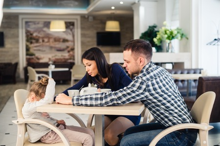 solace: mother gives solace to crying daughter at restaurant and angry father. Stock Photo