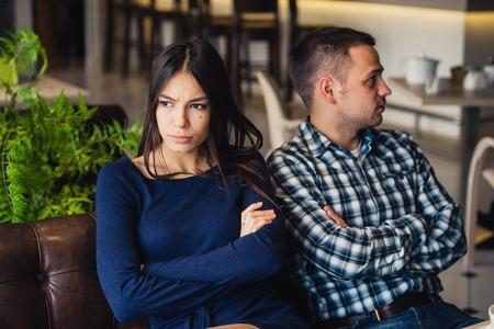 delito: Pareja sentada en el café durante el almuerzo. Están tomando la ofensiva y sentados espalda con espalda. Foto de archivo