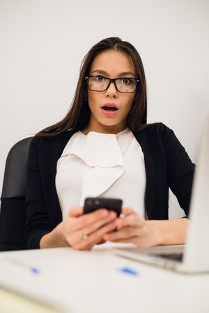 Closeup portrait young, shocked business woman, looking at cell phone seeing bad text message, email, isolated indoors office background. Negative emotions, facial expressions. Stock Photo