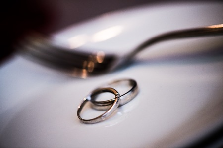 drink me: wedding rings on plate with fork, all on wooden table texture
