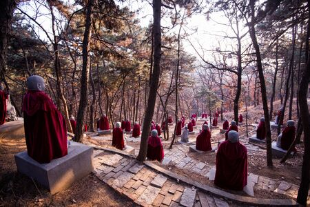 mantles: Stone Monk Statues wearing mantles at chinese forest Stock Photo