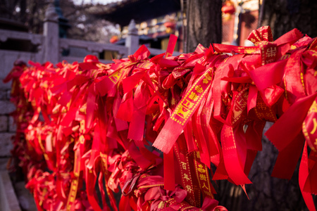Chinese red ribbons on a fence in Buddhist temple.