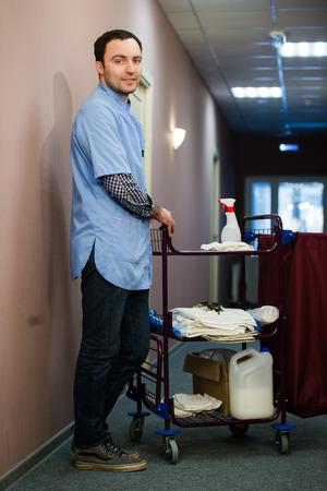 Un homme qui est sur l'hôtel le personnel de nettoyage de l'équipage est souriant avec un aspirateur de serviette dans le processus de nettoyage des chambres d'hôtel et la prestation de services haut-knotch aux invités. Banque d'images