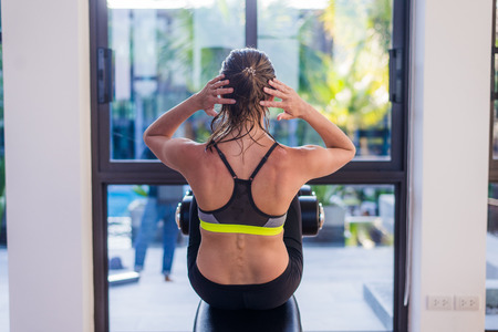 laying abs exercise: Attractive fit woman working out abs in fitness gym at luxury resort hotel with a great view during summer vacation