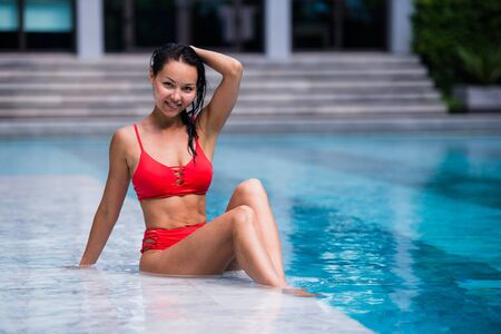 Portrait of beautiful, young lady in red bikini sitting poolside in luxury hotel Stock Photo