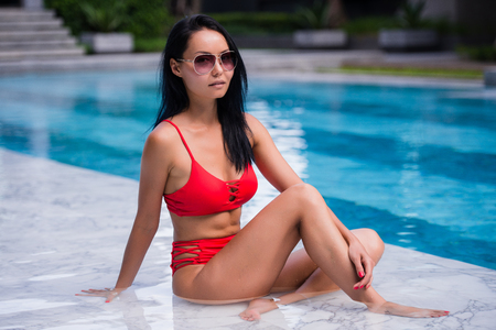 Elegant sexy woman in the red bikini on the sun-tanned slim and shapely body is posing near the swimming pool Stock Photo