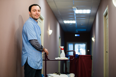 keeping room: A man who is on the hotel cleaning crew staff is smiling with a towel vacuum in the process of cleaning the hotel rooms and delivering top-knotch service to the guests.