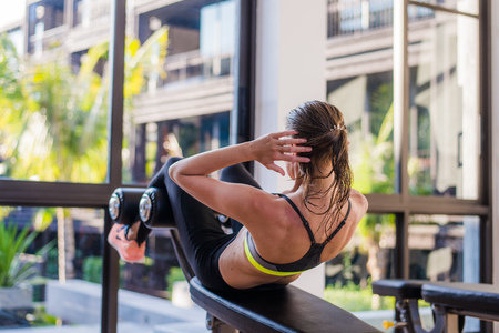 laying abs exercise: portrait of an athletic woman doing exercising abdominals work-out lying in gym at luxury hotel at summer