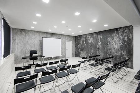 暗い椅子の多くの講議のための部屋。壁が白、ロフトのインテリア。右側にドアがあります。背景には、ラップトップを持つテーブルです。