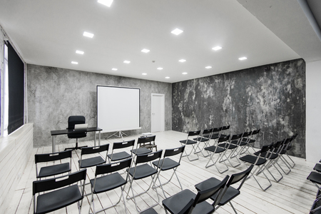 Room for lecture with a lot of dark chairs. Walls are white, loft interior. On the right there is a door. On the background there is a table with a laptop.