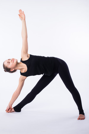 advanced yoga posture, demonstrated by bloden girl, dressed in black, on white background Stock Photo