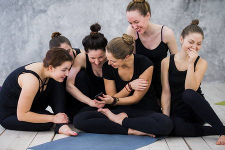 Smiling yogi girl exercising, having a break at class, group of friends watching on the phone
