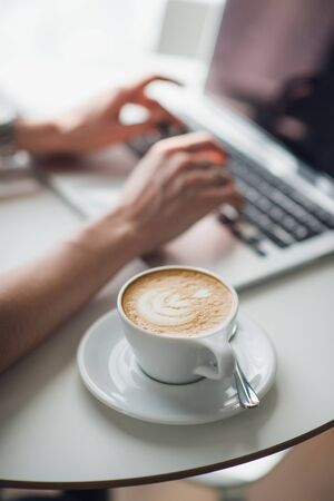 Woman using a laptop during a coffee break, hands close up.