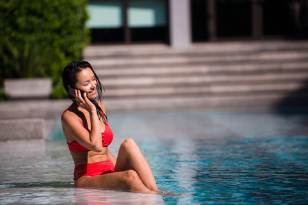 Attractive woman talking on her mobile phone by the poolside