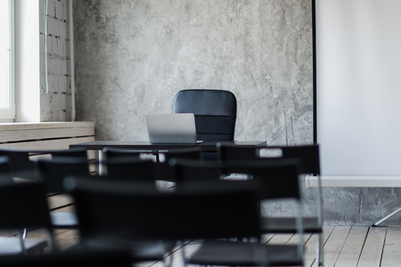 office furniture: Room for lecture with a lot of dark chairs. Walls are white, loft interior. On the right there is a door. On the background there is a table with a laptop.