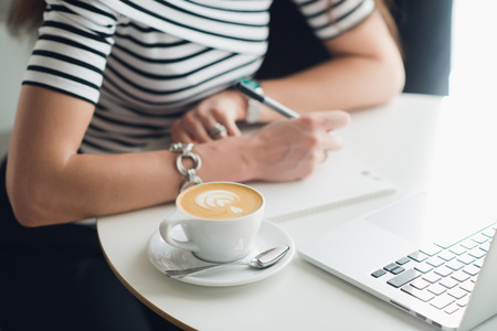 Close up picture of a cup of cappuccino with a pattern and hands writing in a notebook. Woman sitting in a cafe woth a laptop and making notes.