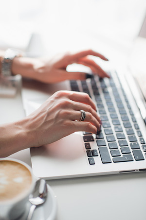 Close up photo of female hands typing on laptop keyboard with a cup of patterned cappuccino.
