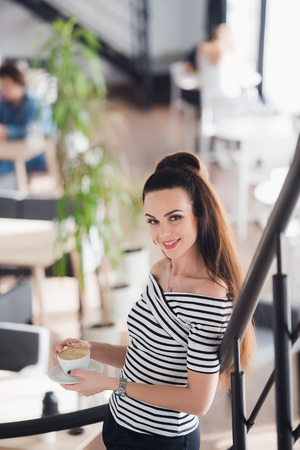 Picture of adult beautiful female standing with a cup of cuppuccino and looking at the camera. Stock Photo