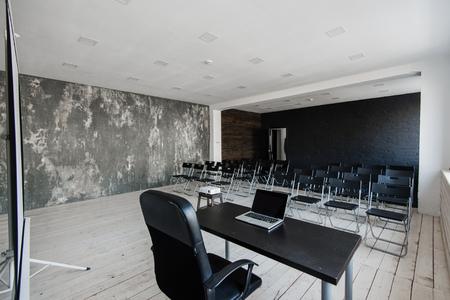 Sala wykładowa z mnóstwem ciemnych krzeseł. Ściany są białe, loftowe wnętrze. Po prawej są drzwi. W tle stół z laptopem.