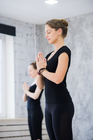 Two women in gym class, relaxation exercise or yoga class
