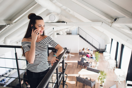 Young owner of a coffee shop or cafe is standing and talking on smartphone while smiling and looking away.