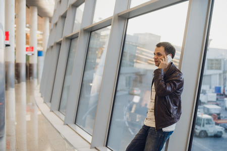 wireless terminals: Traveler inside airport terminal. Young man using mobile phone and waiting for his flight.