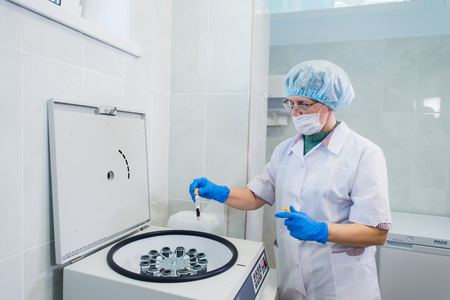 Closeup of a senior female chemist setting up some sample blood tubes inside a centrifuge for some test in a lab.