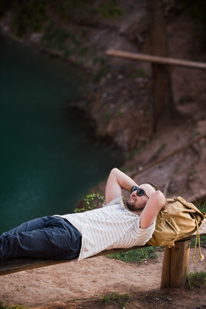 Man Relaxing Outside. Wearing a white T shirt, dark pants, sunglasses, a young guy is lying down on wooden bench against lake in a forest outdoors