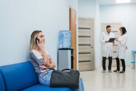 Woman patient in speaking at the mobile phone in hospital waiting room. Standard-Bild