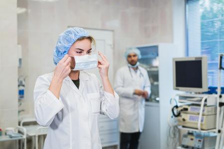 Zelfverzekerde vrouwelijke arts die medisch gezichtsmasker opzet tijdens het voorbereiden op de operatie, haar mannelijke collega staat achter haar Stockfoto
