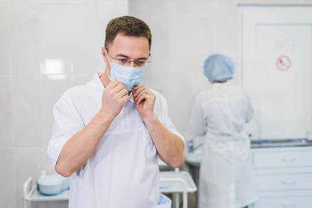 Thoughtful male surgeon wearing surgical mask in hospital
