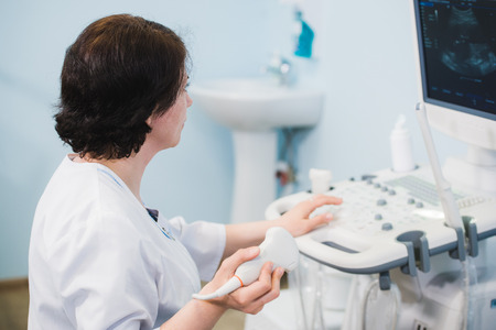 Happy mature female doctor using ultrasound scanner. Echography machine Stock Photo
