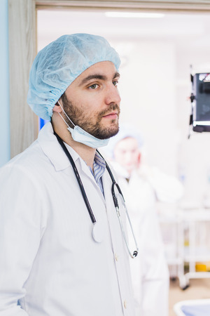 A young handsome pensive man doctor at hospital ward before operation Stock Photo